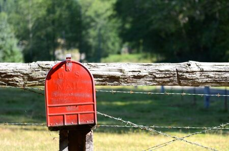 barbed wire fence: USA, Red mailbox on fencepost