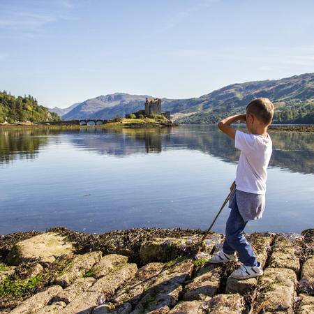 UK, Scotland, Boy (6-7) looking at Eileen Donan Castle