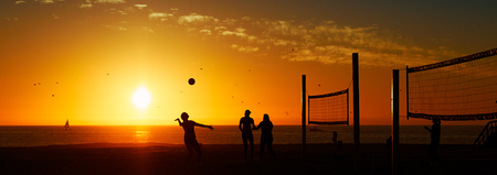 USA, California, Hermosa Beach, Three people playing volleyball, silhouetted against sunset