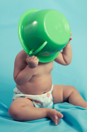 Brazil, Baby boy (6-11 months) with chamber-pot on head