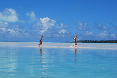 Cook Islands, Children (8-9, 10-11) running in sea