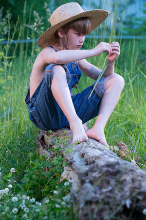 Young boy wearing blue overalls sitting on fallen tree