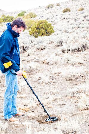 nevada: USA, Nevada, Black Rock Desert, Man using metal detector