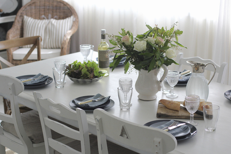 dining table and chairs: Dining table set for lunch with crockery