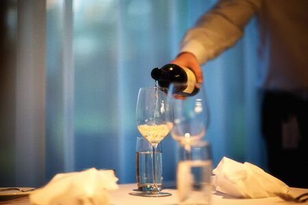 man drinking water: Cropped shot of man in room pouring white wine in wineglass LANG_EVOIMAGES