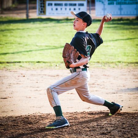 pitching: USA, Young boy (10-11) pitching on pitchers mound