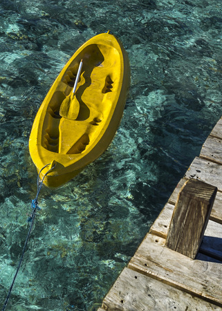 ende: Indonesia, East Nusa Tenggara, Ende, Flores, Empty yellow canoe tied to wooden pier LANG_EVOIMAGES