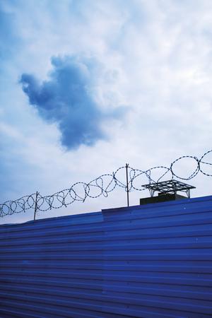 Cloud above razor wire fence