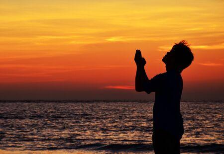 Malaysia, Sabah, Tuaran, Praying man silhouetted against sunset sky over sea