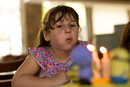 Portrait of girl (4-5) blowing out candles in blurred background