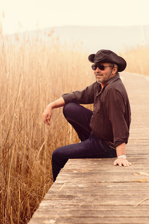 cowboy beard: Portrait of senior man wearing sunglasses and cowboy hat sitting on edge of wooden footbridge