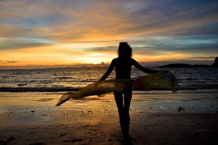 Silhouette of a woman at beach with a sarong LANG_EVOIMAGES