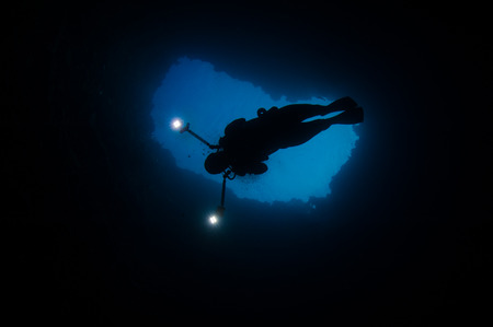 hole: Diver swimming in a blue hole, Palau, Micronesia LANG_EVOIMAGES
