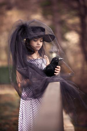 Girl in a black veil  holding a stuffed black bird