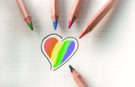 Colored pencils and a drawing of a multi-colored heart