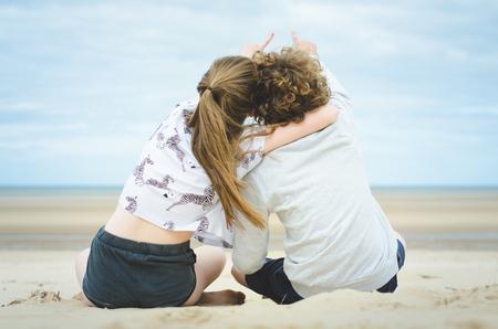 Vista posterior de adolescente y niña sentada en la playa apuntando al cielo LANG_EVOIMAGES