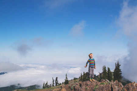 only boys: Boy standing on a mountain peak shouting