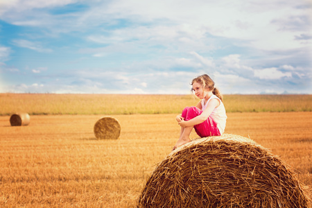 Girl sitting on a straw hay bale LANG_EVOIMAGES