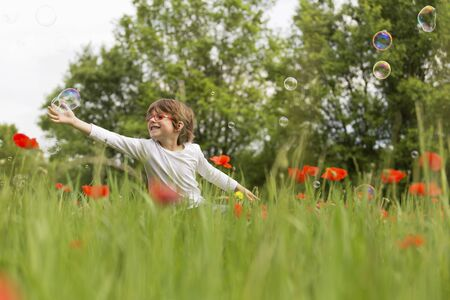only boys: Boy playing with soap  bubbles in a poppy field LANG_EVOIMAGES