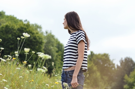 Side view of a women standing in flower field LANG_EVOIMAGES
