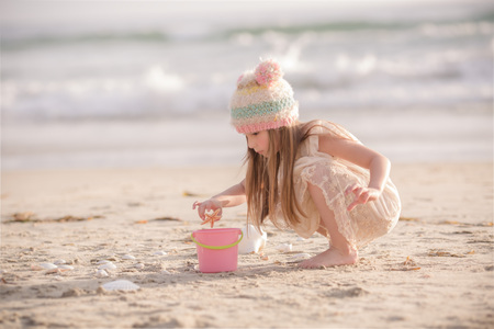 Girl collecting seashells in a bucket LANG_EVOIMAGES