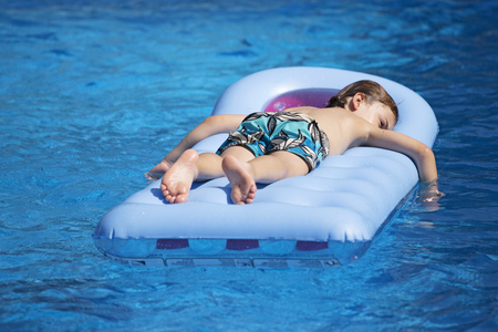 Boy lying on a lilo in a swimming pool LANG_EVOIMAGES