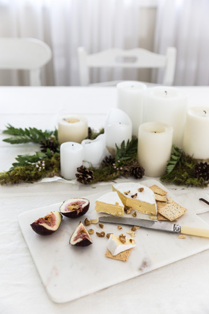 Cheese platter next to a candle centerpiece on dining room table LANG_EVOIMAGES