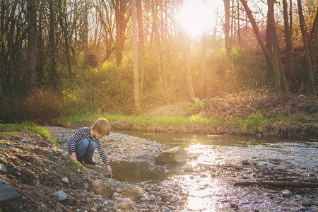 Boy playing at the edge of creek at sunset