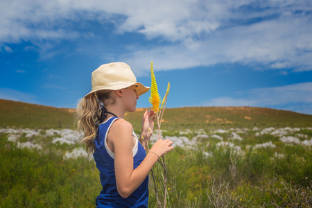 Girl holding wild flowers, Jurien Bay, Western Australia, Australia