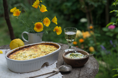 Baked potatoes and cheese on table outdoors with wine and flowers LANG_EVOIMAGES