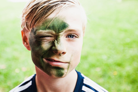 Portrait of a young boy with paint on his face, winking LANG_EVOIMAGES