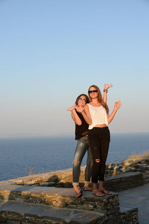 mujer mirando el horizonte: Two girls messing about, Cyclades, Greece