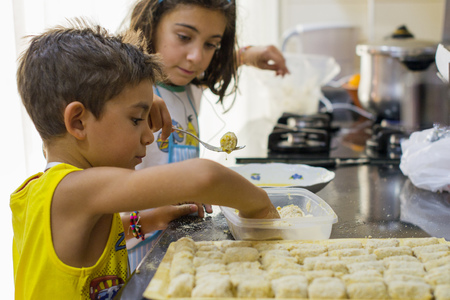 Boy and girl making croquettes in the kitchen