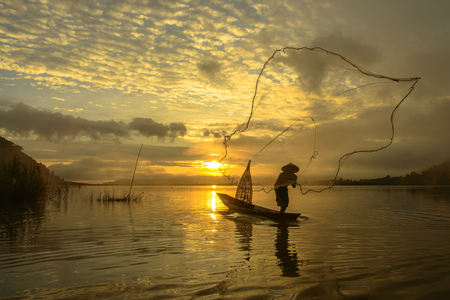 Silhouette of a man throwing fishing net, Lake Bangpra, Thailand LANG_EVOIMAGES