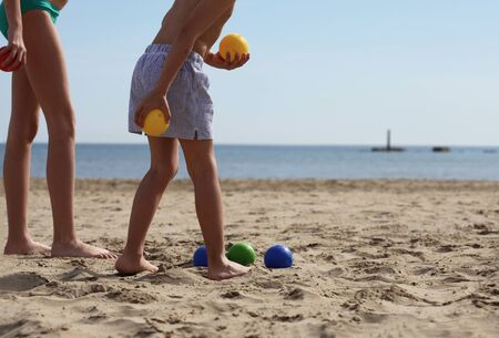 Boy and girl playing boules on the beach