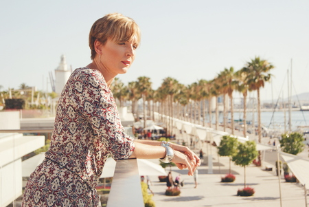 Woman standing on terrace, looking at view, Malaga, Andalucia, Spain