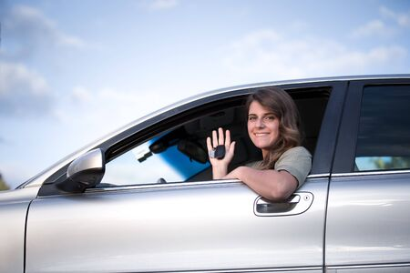 Teenage girl sitting in a car holding up  keys to new car LANG_EVOIMAGES
