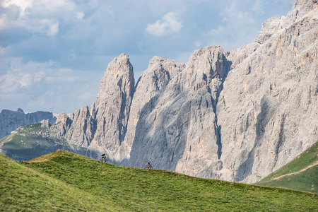 move in: Man and woman riding mountain bikes along trail, Dolomites, Italy LANG_EVOIMAGES