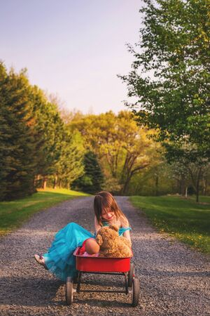 Girl sitting in wagon with doll and teddy bear