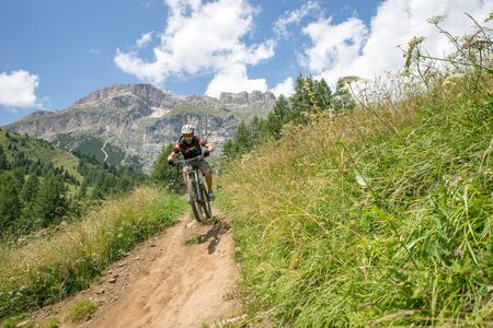 move in: A man riding his mountain bike along trail, Dolomites, italy LANG_EVOIMAGES