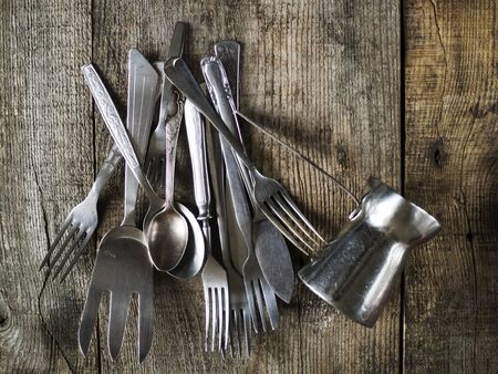 Stack of old vintage cutlery on wooden table LANG_EVOIMAGES