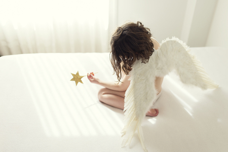 arrodillarse: Girl sitting on bed dressed in angel wings holding star wand