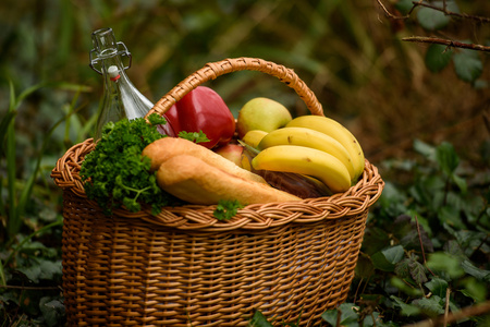 banana bread: Basket with baguette, bottle, bananas, apples, peppers and parsley