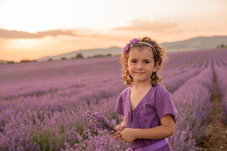 vanishing point: Girl standing in lavender flower field at sunset, Kazanlak, Bulgaria LANG_EVOIMAGES