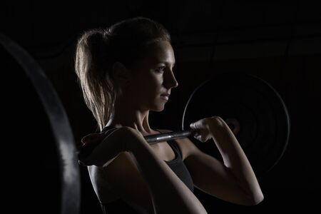 challenges ahead: Young woman lifting barbell in gym LANG_EVOIMAGES