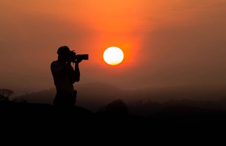 Silhouette of a man taking a photo at sunset
