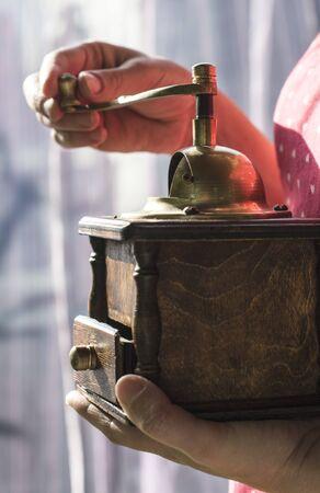 Woman grinding coffee with vintage coffee grinder