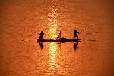 Silhouette of Two fishermen in boat on Mekong river, Thailand
