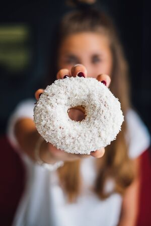 Woman holding a doughnut LANG_EVOIMAGES