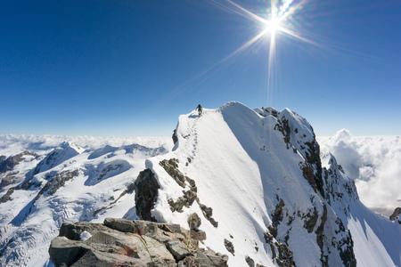 Man reaching the Top of Piz Bernina mountain, Swiss Alps, Graubunden, Switzerland